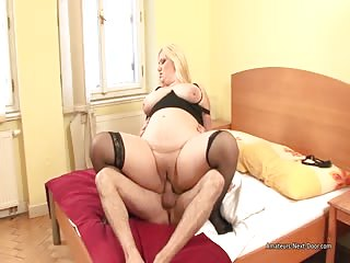 Big round bellied chick in stockings fucks on the bed